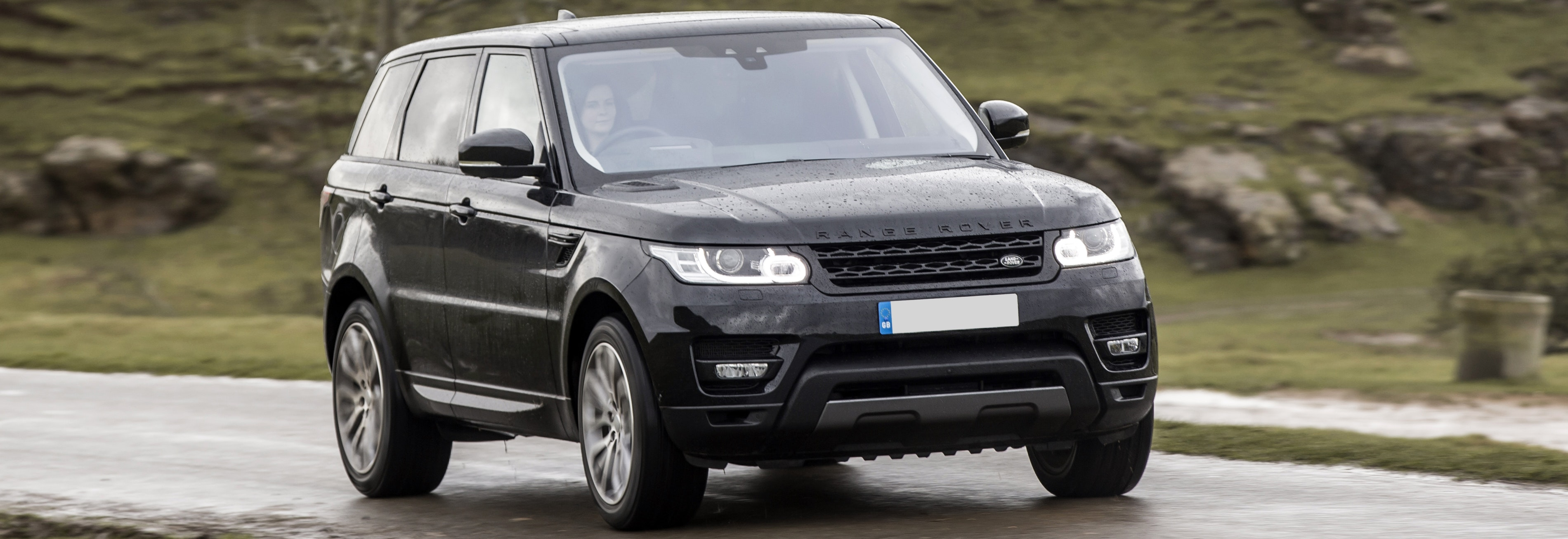 Black Range Rover Sport driving, viewed from the front