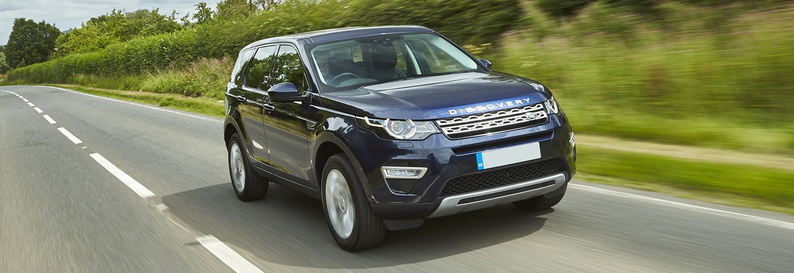 Blue Land Rover Discovery Sport driving, viewed from the front