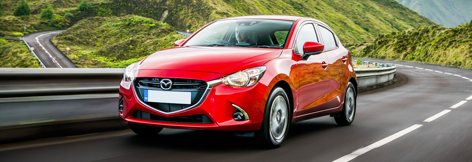 Red Mazda 2 driving, viewed from the front