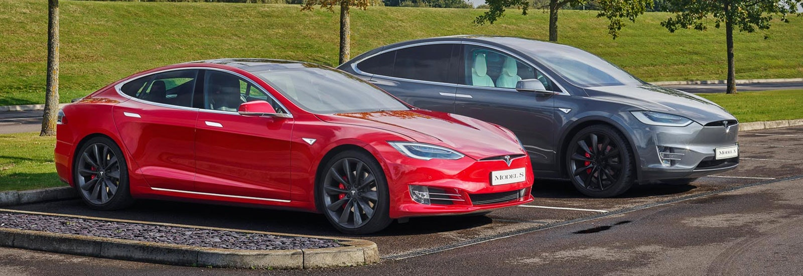 Red Tesla Model S and grey Tesla Model X parked, viewed from the front